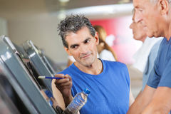 Fitness trainer explaining. Treadmill to senior men in gym Royalty Free Stock Image