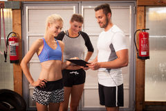 Fitness Trainer explaining exercise. In a gym Royalty Free Stock Image