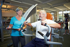Fitness trainer explaining rowing. Machine in gym Stock Photos