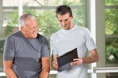 Fitness trainer explaining training. Plan to senior men in gym Royalty Free Stock Photography