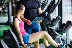 Fitness. Trainer explaining treadmill to jogging woman in gym Stock Photography