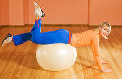 Fitness trainer on a fitball Stock Photos