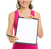 Fitness trainer giving clipboard for sign. Closeup Royalty Free Stock Photo