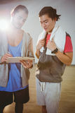 Fitness trainer guiding hid trainee on clipboard Stock Photos