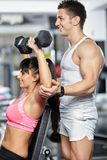 Fitness trainer helping girl in a gym Royalty Free Stock Photos