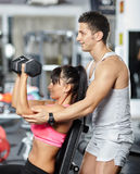 Fitness trainer helping girl in a gym Stock Photography
