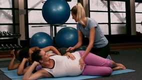 Fitness trainer helping pregnant women train. In slow motion stock video