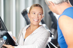 Fitness trainer helping senior on treadmill. Female fitness trainer helping senior on treadmill in a fitness center Stock Images