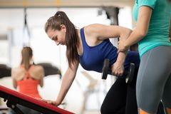 Fitness trainer helping young girl doing exercises in gym Stock Image