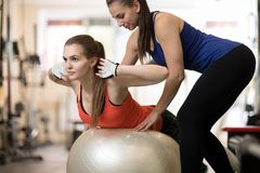 Fitness trainer helping young girl doing back exercises in gym Royalty Free Stock Photos