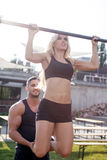 Fitness trainer helps woman pull up Royalty Free Stock Images