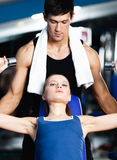Fitness trainer helps woman to exercise Royalty Free Stock Image