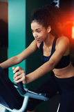 Fitness trainer instructs front of buildings. Half length portrait of cheerful happy woman with afro hair working out on spinning bike at gym Stock Photos