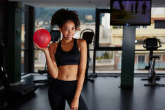 Fitness trainer instructs front of buildings. Portrait of fit afro american woman holding little stability ball at Pilates class in fitness center Royalty Free Stock Photos