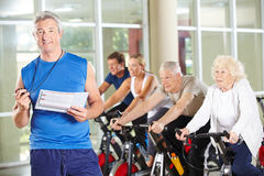 Fitness trainer with senior people. On spinning bikes in gym Royalty Free Stock Photo