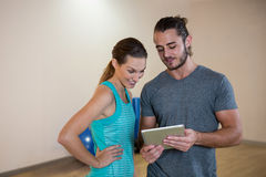 Fitness trainer showing digital tablet to woman. Fitness trainer showing digital tablet to women in fitness studio Royalty Free Stock Photos