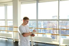 Fitness trainer in sportswear discussing details with new client. Fitness trainer discussing details with new client on smartphone in gym, handsome guy sitting Royalty Free Stock Photo