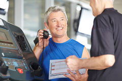Fitness trainer with stopwatch at treadmill Royalty Free Stock Photos
