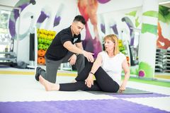 Fitness trainer and student. 32 year old male trainer works with his 67 year old female student, in a fitness studio setting Royalty Free Stock Photos