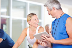 Fitness trainer with tablet PC talking to woman Stock Photography