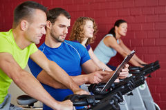 Fitness trainer talking to man on. Fitness trainer with clipboard talking to a men on spinning bike Royalty Free Stock Photography