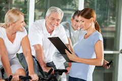 Fitness trainer talking to senior. Citizens on bikes in gym Royalty Free Stock Images