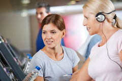 Fitness trainer talking to senior. Women on treadmill in gym Stock Photo