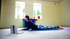 Fitness trainer use video call for personal yoga class. Smiling woman begins on online training with sphinx pose. Girl teaches proper exercise. Female has dark stock footage