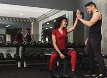 Fitness trainer and woman giving each other high five. Successful training. Fitness trainer and women giving each other high five after workout in gym, copy stock images