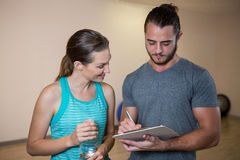 Fitness trainer and woman looking at clipboard Royalty Free Stock Photography