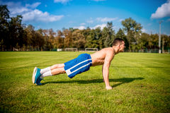Fitness trainer working out on football field. Healthy gym training outdoors