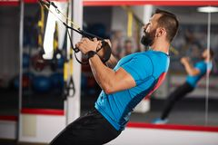 Crossfit workout with trx straps. Fitness trainer working with trx straps for crossfit workout Royalty Free Stock Photo