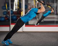Crossfit workout with trx straps. Fitness trainer working with trx straps for crossfit workout Stock Photos