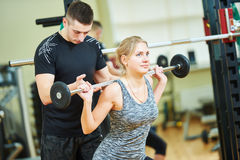 Fitness trainer works with woman in gym. Personal trainer helping women working with barbell weght Stock Image