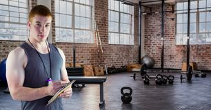 Fitness trainer writing on clipboard in gym. Digital composite image of fitness trainer writing on clipboard in gym Stock Images