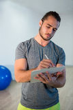 Fitness trainer writing on clipboard Royalty Free Stock Image