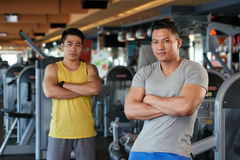 Fitness trainers. Asian smiling fitness instructors standing with their arms crossed and looking at camera royalty free stock photos