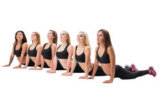Fitness trainers exercising together in studio. Young and pretty fitness trainers in black tops and leggings doing exercises in studio Stock Images
