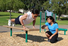 Fitness Training. Father on park exercise bench and his daughter timing his push ups royalty free stock photos