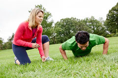 Fitness training. A female fitness coach training a male athlete doing push ups Royalty Free Stock Photos
