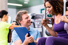 Fitness training in gym - black woman and personal trainer. Fitness training in gym - black women and personal trainer exercising on resistance machine Royalty Free Stock Photography