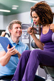 Fitness training in gym - black woman and personal trainer royalty free stock images