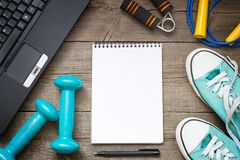 Fitness training and healthy lifestyle blog background with notebook and dumbbells Royalty Free Stock Image