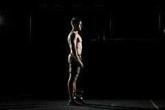Fitness training. Man doing exercises with weights. In dark gym Stock Photos