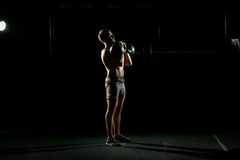 Fitness training. Man doing exercises with weights. In dark gym Stock Images