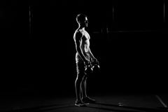 Fitness training. Man doing exercises with weights. In dark gym Royalty Free Stock Images