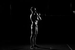 Fitness training. Man doing exercises with weights. In dark gym Stock Photography