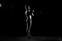 Fitness training. Man doing exercises with weights. In dark gym Stock Image