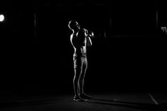 Fitness training. Man doing exercises with weights. In dark gym Royalty Free Stock Photography