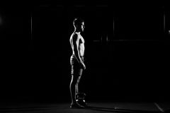 Fitness training. Man doing exercises with weights. In dark gym Stock Photo